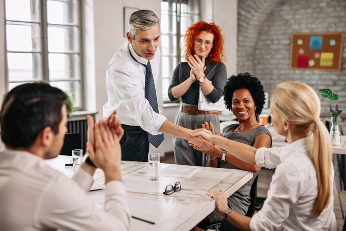 Two happy business people shaking hands on a meeting while other colleagues are applauding them in the office.