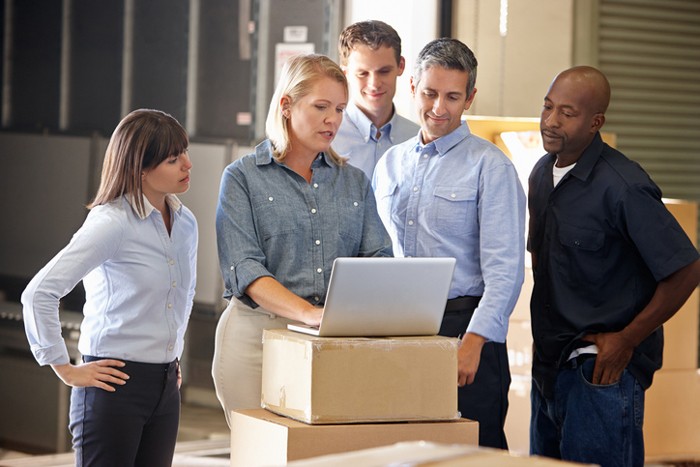 Five Workers In Distribution Warehouse Looking At Laptop